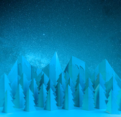 Winter paper landscape with mountains and pine trees at night