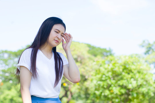 Young Asian woman is feeling sickness when staying at the park.