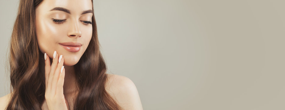 Close up face of beautiful woman with clear skin on beige background