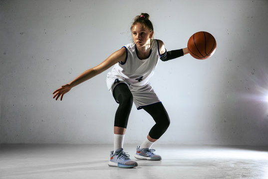Young caucasian female basketball player of team in action, motion in run isolated on white wall background. Concept of sport, movement, energy and dynamic, healthy lifestyle. Training, practicing.