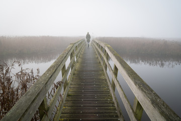 A woman walking on a small footbridge on a foggy day in autumn.