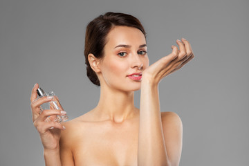 perfumery, beauty and luxury concept - happy young woman smelling perfume from her wrist over grey background