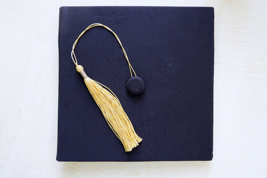 Navy blue graduation cap with yellow tassels on it. Detail shot from the top.