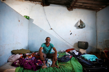 Felix poses for a picture in his accommodation after working on a coffee farm, during a labor ministry operation to identify workers in conditions analogous to slavery, in Campos Altos