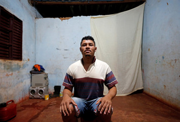 Jesus poses for a picture in his accommodation after working on a coffee farm, in Campos Altos