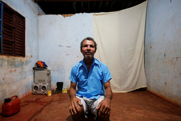 Paulo Santos de Jesus poses for a picture in his accommodation after working on a coffee farm, in Campos Altos