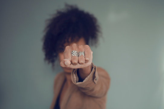 Closeup and selective focus on a black woman fist (with rings). Afro puff hair.