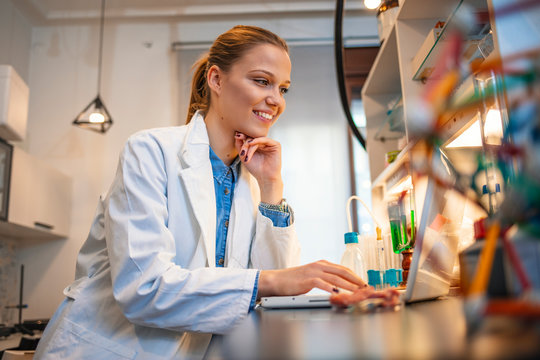 Young female scientist working on the computer in a laboratory. Female researcher taking notes at her workplace. She is standing in her laboratory, using microscope and laptop for her research.