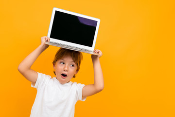 surprised boy holds a laptop on his head with a mockup on a yellow background with copy space