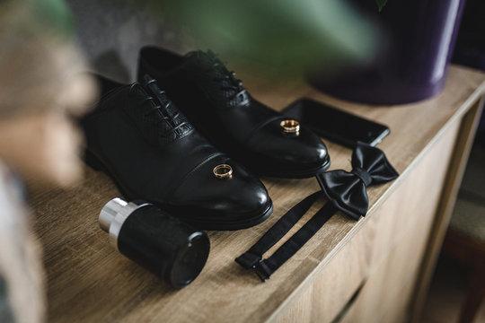 The groom is gathering in the morning. wooden shelf. Men's Black classic patent leather shoes. A black bow tie. Wedding details. Eau de toilette, black perfume, black mobile phone