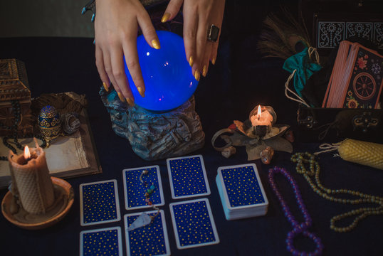 Tarot cards and crystal ball, candles, witch magic bottles . Wicca, esoteric, divination and occult background with vintage magic objects for mystic rituals