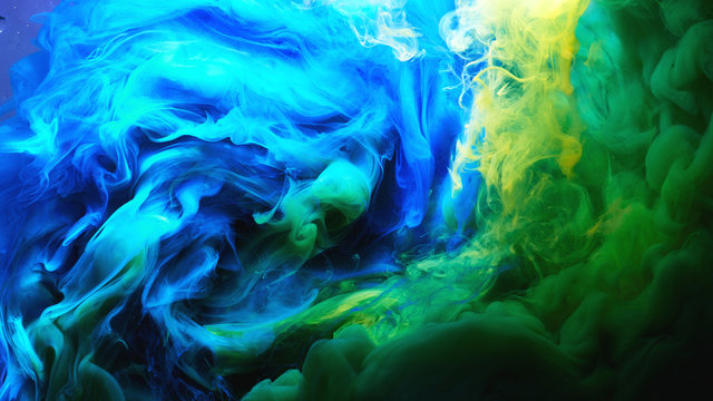 Abstract dancing colorful fume background. Clouds of smoke blue, green and yellow, a whirlwind of paints
