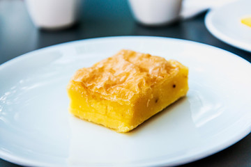 Fototapete - Delicious sweet orange cake, traditional greek pastry baked with orange pieces and honey, served in white plate.