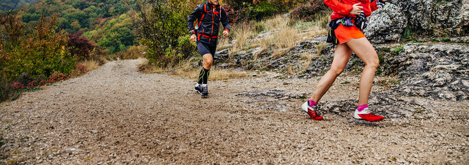 woman and man runners run mountain trail in autumn cloudy weather