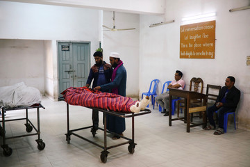 Relatives are seen at the morgue of Dhaka Medical College Hospital after a deadly fire in a plastic factory in Dhaka