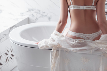 Rear view of a slim unidentified girl in white erotic lingerie sitting on the edge of the bathroom in luxury apartments. The concept of sexy lingerie and a seductive female figure