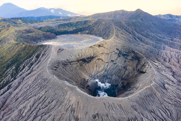 View from above, stunning aerial view of the Mount Bromo with clouds of gases raising from the crater. Mount Bromo is an active volcano in East Java, Indonesia. Fototapete