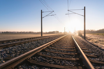 Railroad tracks and frosty landscape. Rail tracks at sunrise