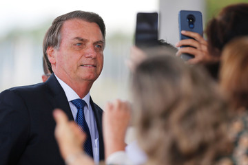 Brazil's President Jair Bolsonaro poses for pictures as he leaves the Alvorada Palace in Brasilia