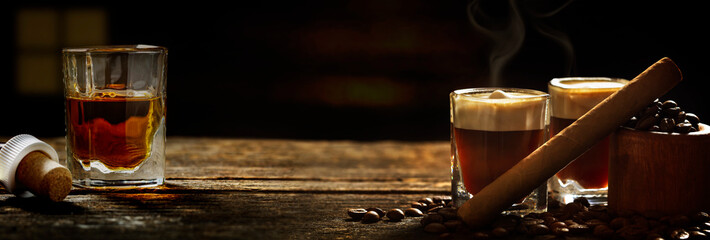 Irish coffee - coffee and whiskey and cigars against dark background