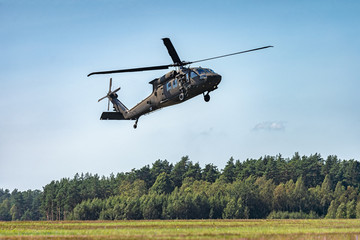 Military helicopter flying in the sky with forest at the background