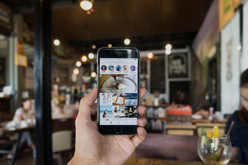 CHIANG MAI, THAILAND - SEP 04, 2017: A man hand holding iphone with search page screen of instagram application. Instagram is largest and most popular photograph social networking.