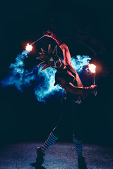 Man in red jester costume with double fire torch performing some action moment with some blue smoke in the dark