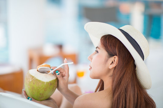 Portrait of a beautiful woman relaxing with coconut juice at the swimming pool outdoors