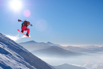 Stores à enrouleur Glisse hiver Snowboarder Jumping on Red Snowboard in Mountains at Sunny Day. Snowboarding and Winter Sports