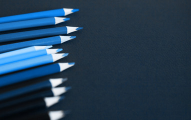 Colored pencils against dark blue background. Close up and selective focus.
