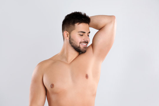 Young man showing hairless armpit after epilation procedure on light grey background