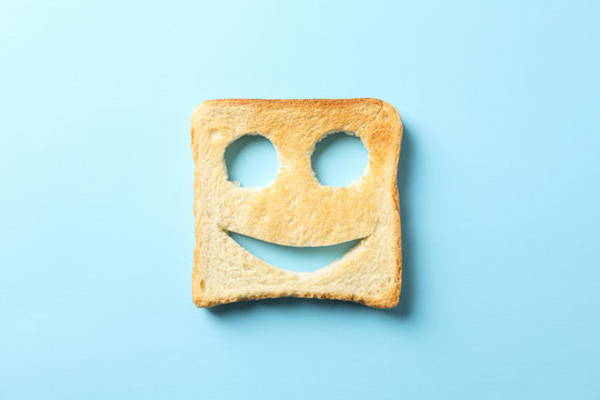 Tasty bread toast with happy face on blue background, top view