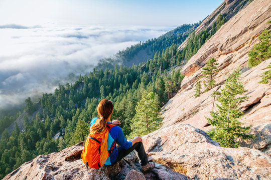A woman above the clouds on the second Flatiron, Boulder, Colorado, USA