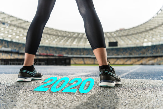 cropped view of sportswoman standing on running track near 2020 lettering