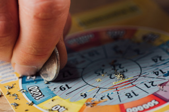 cropped view of gambler scratching lottery ticket with silver coin