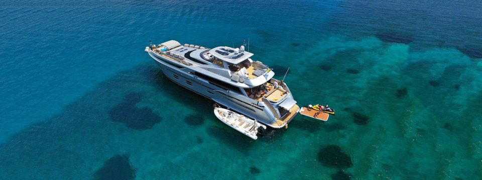 Aerial drone ultra wide photo of luxury yacht docked in tropical exotic island with turquoise sea