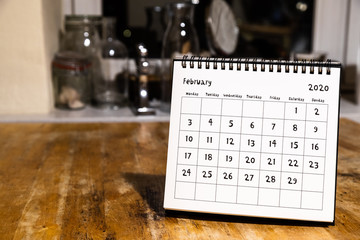 February 2020 calendar - month page on wooden table in the kitchen