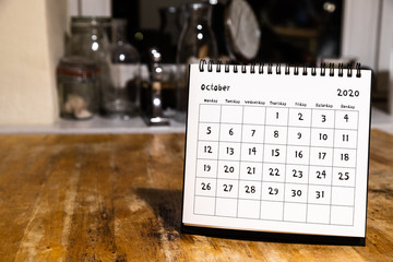 October 2020 calendar - month page on wooden table in the kitchen