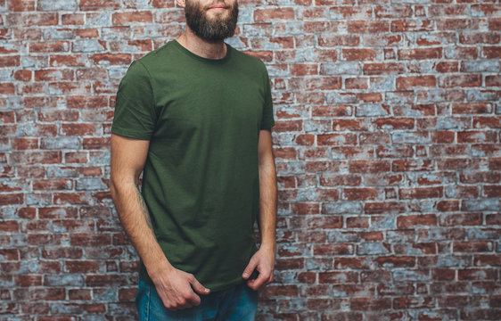 City portrait of handsome hipster guy with beard wearing a blank green military t-shirt standing on a brick wall background. Empty space for your logo or design. Mockup for print.