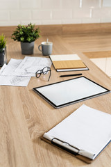 Clipboard, tablet and plan on wooden kitchen counter