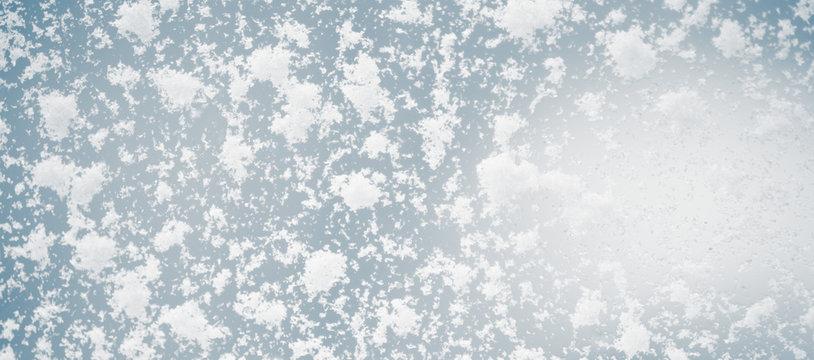 Large snow flakes on the window, macro photo.