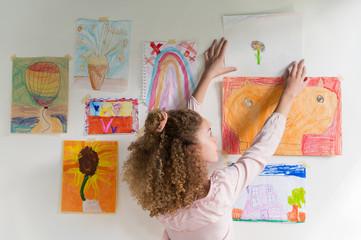 Girl hanging artwork on wall