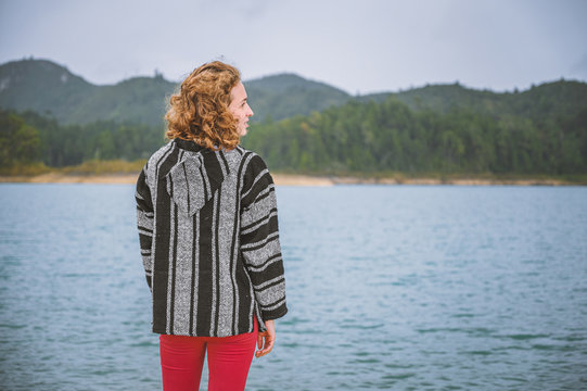 Young woman watching the landscape of a lagoon with mountains in the background and cloudy sky
