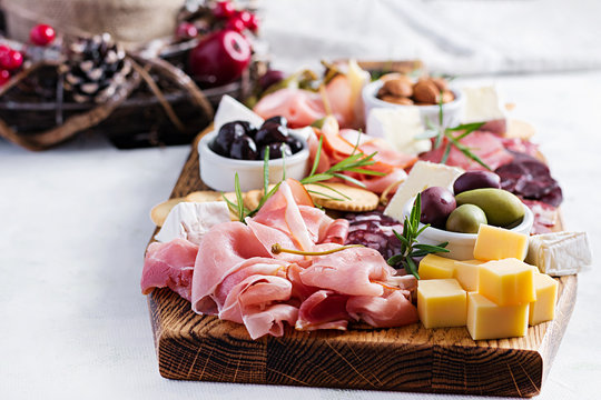 Antipasto platter with ham, prosciutto, salami, cheese,  crackers and olives on a light background.  Christmas table.