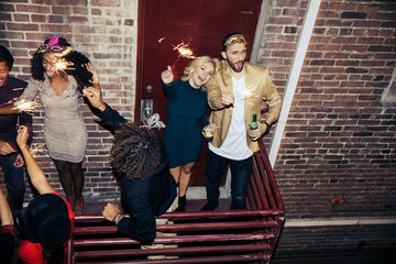 High angle view of friends enjoying party on balcony at night