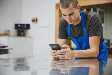 Worker using smart phone while leaning on metallic table in  factory