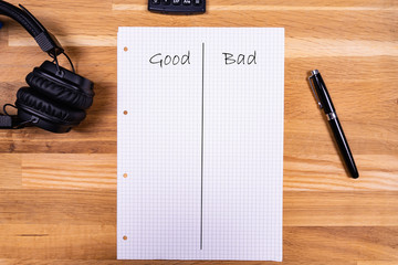 "A notepad with a note saying ""Good Bad"" together with a pen, a calculator and headphones on a wooden table"