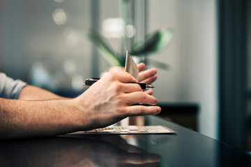 Cropped image of businessman's hands holding credit card and pen at reception desk in hotel
