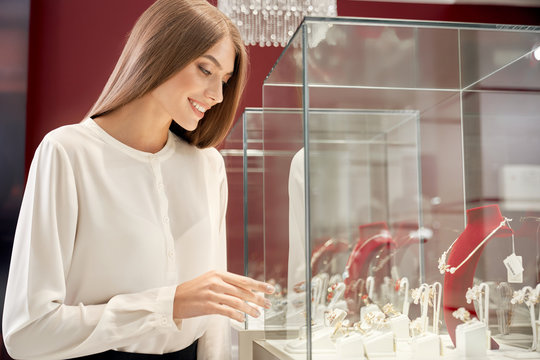 Beautiful girl looking at window case with luxury jewelry
