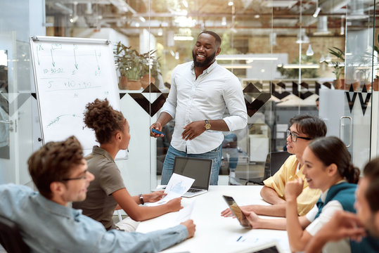Great work. Young afro american businessman pointing at white blackboard and smiling while working with multicultural team in the creative office